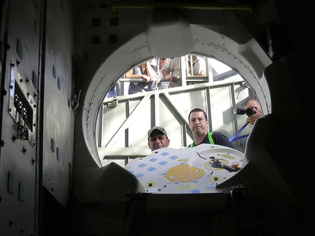 Patch-eye view: NASA techs look into space shuttle Endeavour's crew cabin after storing patches and a photo on board for the orbiterâs final ferry flight.