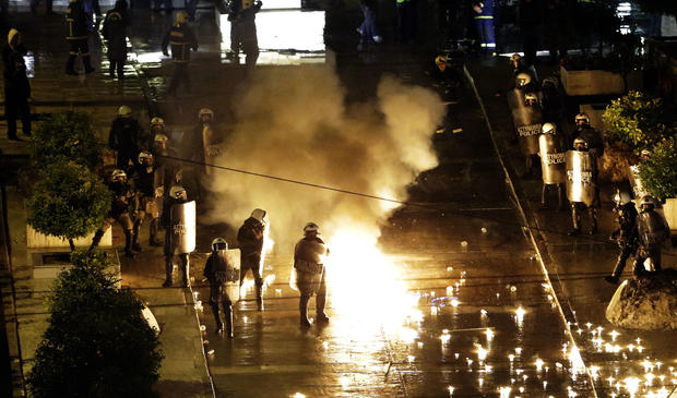 A petrol bomb thrown by protesters explodes near riot police in front of parliament on Wednesday, Nov. 7, 2012, during clashes in Athens, Greece.