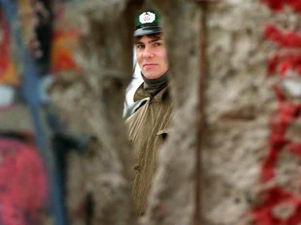 An East German policeman looks through a hole in the Berlin Wall on Nov. 21, 1989.