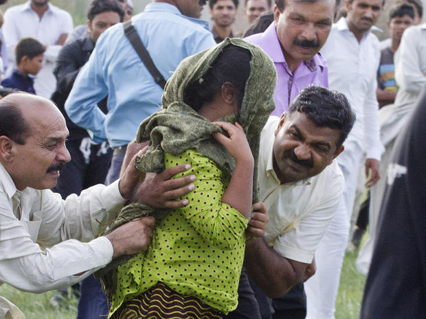 A young Christian girl accused of blasphemy is escorted to a helicopter after her release from prison