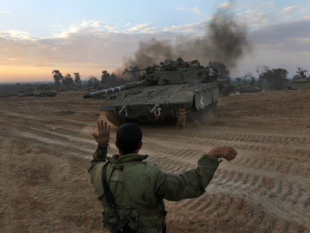 An Israeli soldier guides a tank to a new position at a staging area near the Israel-Gaza Strip border
