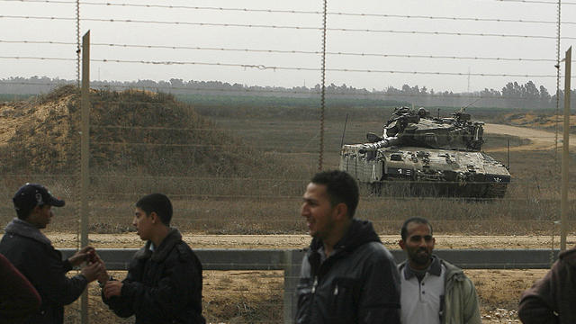 Israeli tank keeps watch over the Gaza border as Palestinians gather near the fence on the other side