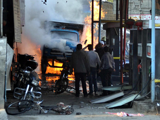 Syrians stand near a burning truck that was destroyed by two car bombs in the Jaramana suburb of Damascus, Syria, Nov. 28, 2012, in this photo released by the Syrian official news agency SANA.