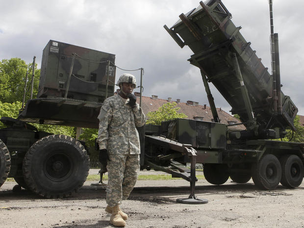 A U.S. soldier stands next to a Patriot surface-to-air missile battery