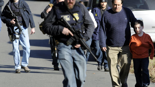 Parents leave a staging area after being reunited with their children following a shooting at the Sandy Hook Elementary School in Newtown, Conn., Dec. 14, 2012.
