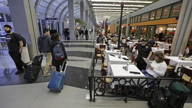 A diner at Wolfgang Puck Cafe in  O'Hare International Airport in Chicago sits in a sidewalk cafe setting in Terminal 3.