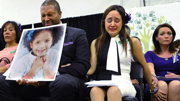 Jimmy Greene, foreground left, Nelba Marquez-Greene, center, parents of Sandy Hook Elementary School shooting victim Ana Marquez-Greene, and Nicole Hockley, right, mother of victim Dylan Hockley, react during a news conference at Edmond Town Hall in Newto
