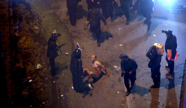 Egyptian riot police beat a man, after stripping him during clashes next to the presidential palace, Friday, Feb. 1, 2013, in Cairo.