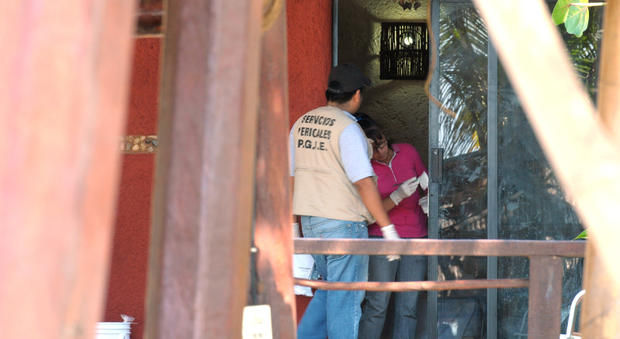 Police investigators work to obtain fingerprints on a door at the home where masked, armed men broke in, in Acapulco, Mexico, Feb. 5, 2013.