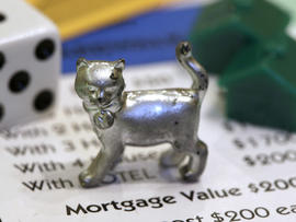 The newest Monopoly token, a cat, rests on a Boardwalk deed next to a die and houses at Hasbro Inc. headquarters, in Pawtucket, R.I., Tuesday, Feb. 5, 2013. Voting on Facebook determined that the cat would replace the iron token.