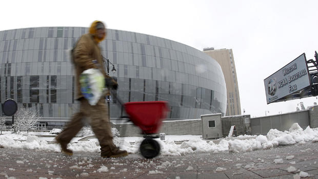 A man spreads salt on the sidewalk across the street from the Sprint Center, Sunday, March 24, 2013, in Kansas City, Mo. The man was preparing for the third round of the NCAA college basketball tournament at the arena after the region received 6-10 inches of snow overnight.