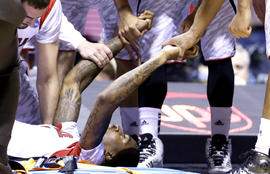 Louisville players talk to guard Kevin Ware after Ware's injury during the first half of the Midwest Regional final against Duke in the NCAA college basketball tournament, Sunday, March 31, 2013, in Indianapolis.