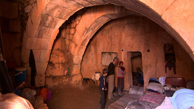 """Syrians stand inside their cave home in Jabel Zawiya's """"Dead Cities"""""""