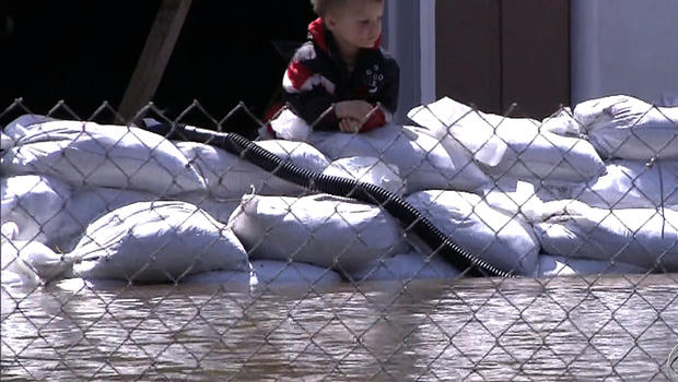 """A boy in the Midwest watches water from a flooded river in a """"CBS Evening News"""" segment broadcast April 27, 2013."""