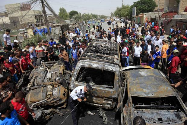 People gather at the scene of a car bomb attack in the Sadr City neighborhood in Baghdad