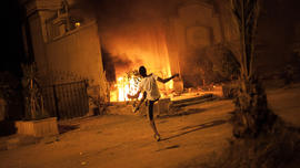 An Egyptian protester attacks Muslim Brotherhood headquarters in Muqattam district in Cairo, Sunday, June 30, 2013.
