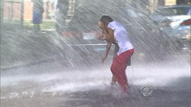 A child find relief from triple-digit weather in Chicago by running through water on July 17, 2013.