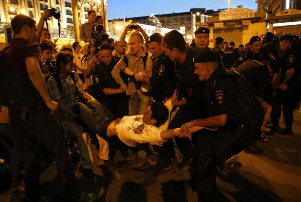 Police detain a protestor as people gather in support of opposition figure Alexei Navalny in the center of Moscow