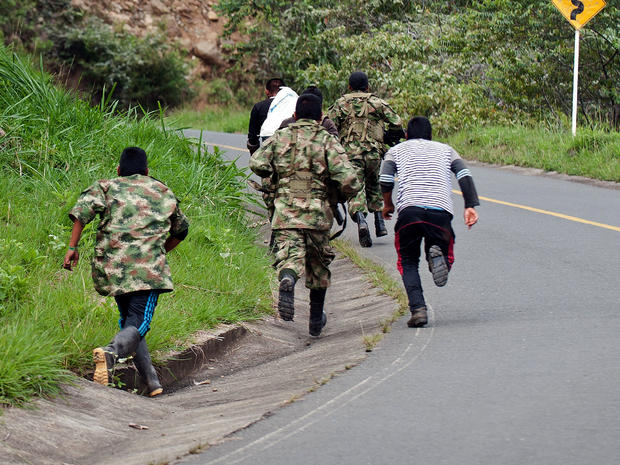 Revolutionary Armed Forces of Colombia (FARC) guerrillas run as the police nears, in the rural area of Caloto, department of Cauca, Colombia, on June 4, 2013, after putting mines along the road between Caloto and Toribio.