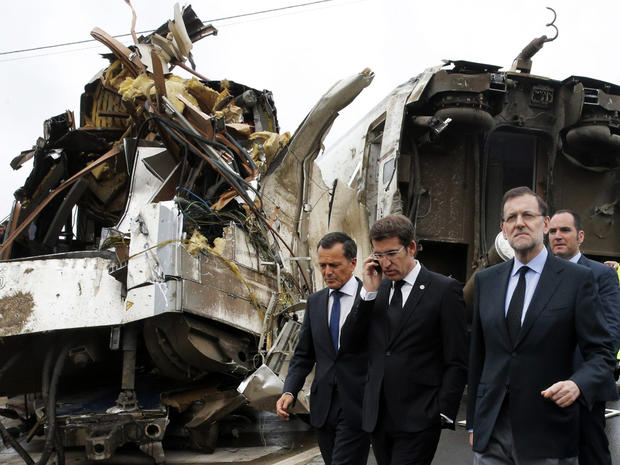 Spanish Prime Minister Mariano Rajoy, right, and Galicia's regional president, Alberto Nunez Feijoo, second left, visit the site of a train accident near the city of Santiago de Compostela, Spain, July 25, 2013.