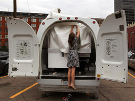 Amelia Langer, an assistant curator of Draft Urbanism, the art exhibition of the 2013 Biennial of the Americas, unzips the opening to a hotel room made of aluminum and inflated vinyl capable of being held aloft by a van-mounted scissor lift on promotional display in a parking lot in downtown Denver July 25, 2013.