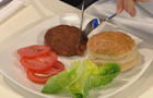 A food expert cuts into a patty of beef grown entirely from bovine stem cells
