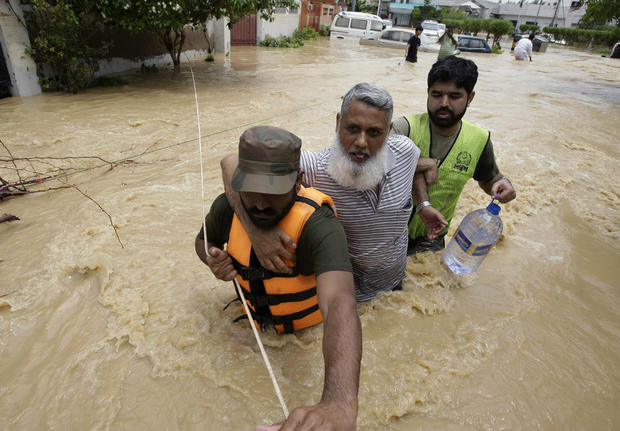 Pakistani soldiers rescue a resident from an area flooded by heavy rains on the outskirts of Karachi, Pakistan