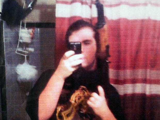 Michael Brandon Hill poses in this undated photo provided by the Dekalb County Police Department with an AK-47-style rifle that authorities believed is the one he had when he was arrested at a Decatur, Ga., elementary school Aug. 20, 2013.
