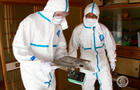Akira Okawara and Seth Doane wear protective suits to travel to Okuma.