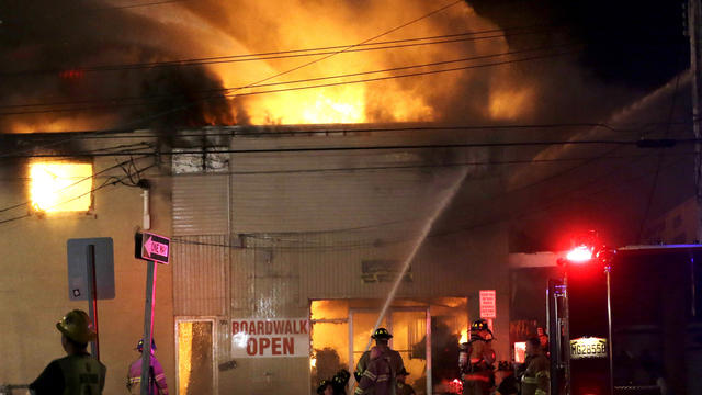 Firefighters battle a blaze in a building on the Seaside Park boardwalk on Thursday, Sept. 12, 2013, in Seaside Park, N.J. The fire began in a frozen custard stand on the Seaside Park section of the boardwalk and quickly spread north into neighboring Seas