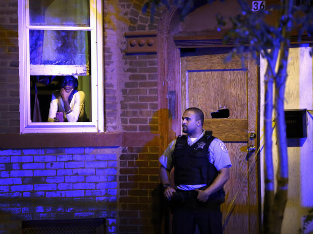 A police officer stands guard outside a home in Chicago where a man was shot in the chest in the Humboldt Park neighborhood on the city's West Side Sept. 20, 2013.