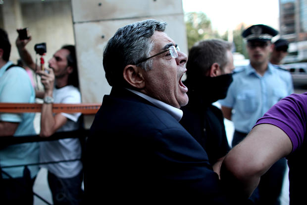 The leader of ultra-right wing Golden Dawn party Nikos Michaloliakos is escorted by masked police officers