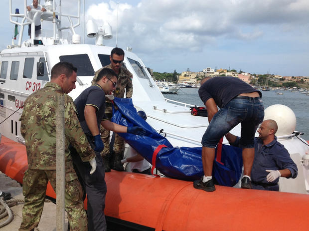 The body of a drowned migrant is unloaded from a Coast Guard boat in the port of Lampedusa