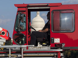 A firefighter sits in a firetruck near the scene on the National Mall in Washington where a man set himself on fire Oct. 4, 2013.