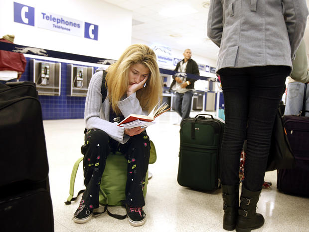 Jamie Collier, 18, is engrossed in her book while waiting to board her bus at the Raleigh Greyhound Station in downtown Raleigh, N.C., Nov. 26, 2013.