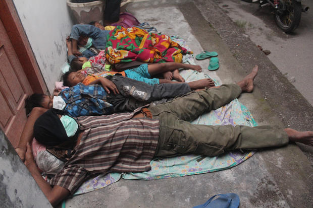 Villagers sleep at a temporary shelter after they were evacuated from their homes