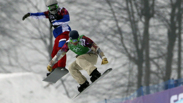 Alex Deibold of the United States, right, and Paul-Henri de le Rue of France fly over the last jump in the men's snowboard cross final