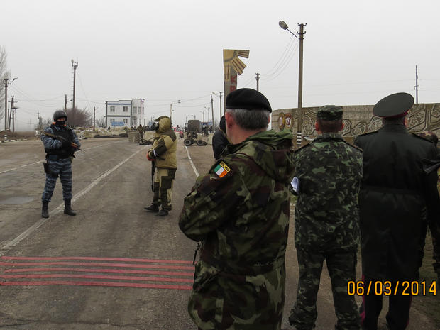 Members of an Organisation for Security and Cooperation in Europe (OSCE) military observer mission (at right, facing away from camera) are stopped at the Crimean border by unknonw armed men