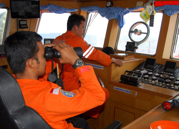 A member of Indonesian National Search And Rescue Agency (BASARNAS) uses binoculars to scan the horizon during a search operation for the missing Malaysia Airlines Boeing 777