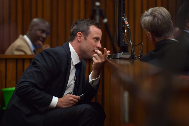 Oscar Pistorius speaks with a member of his legal team prior to a hearing of his trial at the North Gauteng High Court in Pretoria