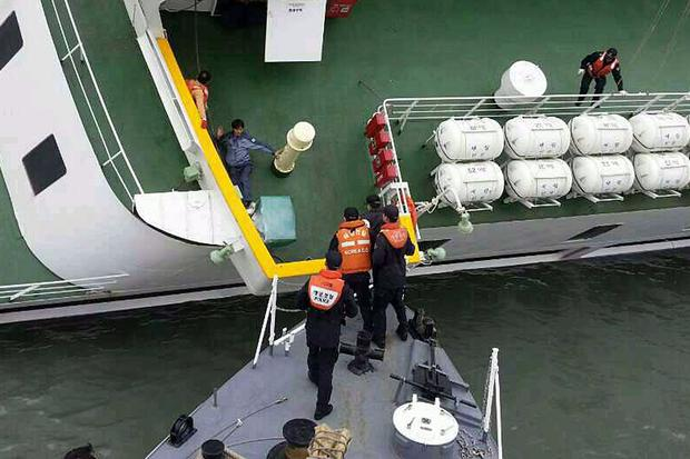 A passenger is rescued by South Korean maritime policemen from the sinking ship Sewol in the sea off Jindo April 16, 2014, in this picture provided by the Korean coast guard and released by Yonhap.