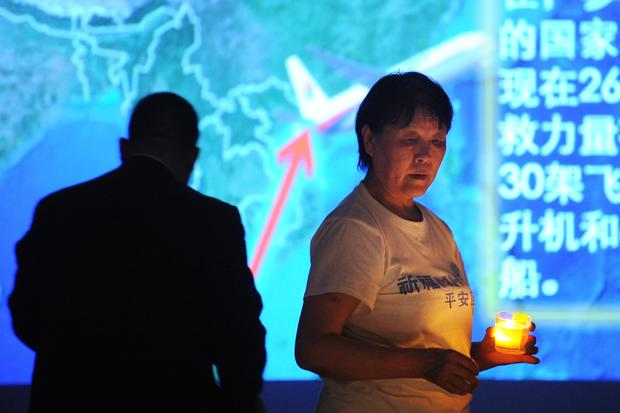 A Chinese relative (R) of passengers on the missing Malaysia Airlines flight MH370 holds a candle as she takes part in a prayer service at the Metro Park Hotel in Beijing