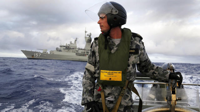 Standing in a rigid hull inflatable boat launched from the Australian navy ship HMAS Perth, Leading Seaman, Boatswain's Mate, William Sharkey searches for possible debris in the southern Indian Ocean in the continuing search for the missing Malaysia Airli
