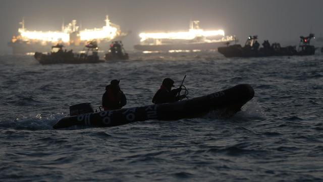 South Korean rescue workers search the area where the capsized passenger ferry Sewol sank, as fishing boats emit light