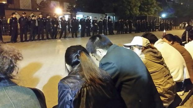 Family members (front) of passengers aboard missing Malaysia Airlines flight MH370 gather for a sit-in protest as security personnel stand guard outside the Malaysian Embassy in Beijing