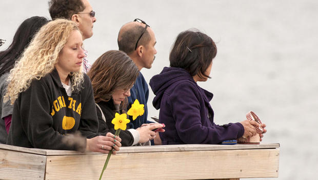 People gather on the beach for a vigil in honor of slain student Maren Sanchez in Milford, Connecticut, April 25, 2014.