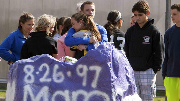 Students mourn in front of Jonathan Law High School in Milford, Connecticut, April 25, 2014. A 16-year-old girl was killed in an attack inside the school.