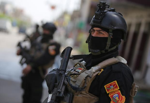 Members of Iraq's anti-terrorism force stand guard outside a polling station in Baghdad