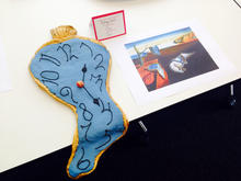"A cake inspired by Salvador Dali's ""The Persistence of Memory"" is seen next to a picture of the painting."