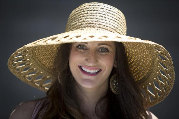 Jaqueline Williams poses for a portrait with her hat before the 146th running of the 2014 Belmont Stakes in Elmont, New York, June 7, 2014.